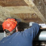 18 A volunteer installing insulation along the basement rim joists