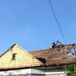 A worker removes roof sheathing