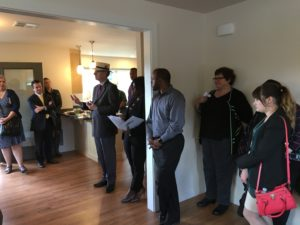 Portland Housing Bureau Director Kurt Creager (with hat) congratulates PCRI on the complete homes